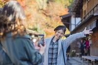 秋の宿場町で写真を撮る日本人女性