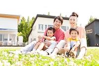 住宅街の草原に座る家族