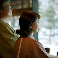 旅館の窓から外の眺めを楽しむシニア夫婦