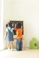 黒板を指差す男の子と女の子