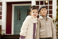 家の前に立つ男の子と女の子