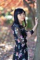 樹に手を添え見つめる日本人女性