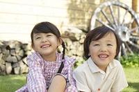 芝生に座って遊ぶ笑顔の女の子と男の子