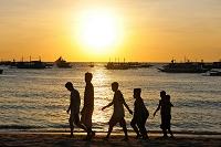夕暮れのビーチを歩く子供のシルエット