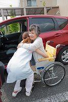 車への乗車を介助する介護士