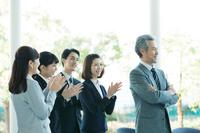 腕を組むビジネスパーソンと拍手をする日本人ビジネスパーソン