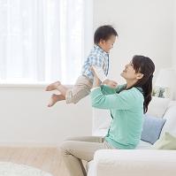 ソファに座って息子を抱き上げる母親