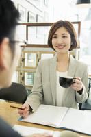 カフェでミーティングをするスーツ姿の日本人女性