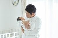 新生児を抱っこするお父さん