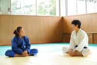 畳の上で準備運動をする女子柔道選手