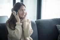 ソファで音楽を聴く女性