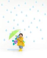 カッパを着て傘をさす日本人の男の子