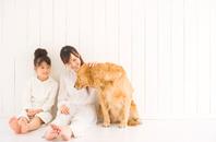 壁にもたれて座る母娘と犬