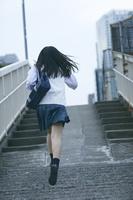 歩道橋を走る女子高生
