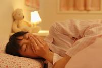 ベッドで咳をする体調不良の女の子