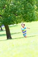 公園をボールを持って走る日本人の男の子