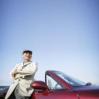 オープンカーに寄りかかるシニアの日本人男性