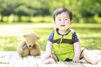 公園の芝生に座る男の日本人の赤ちゃん