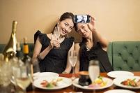 友人と並んでスマホを見る日本人女性