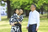 公園で新緑を見上げるおじいちゃんと娘と孫