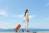 スーツケースを引いて歩く日本人女性