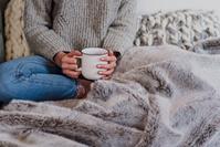 毛布の上でティーカップを持つ女性