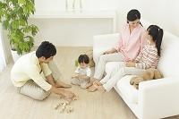 リビングでくつろぐ両親と子供とトイプードル