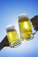 青空の中でジョッキビールで乾杯
