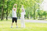 新緑と柔軟体操するシニア夫婦