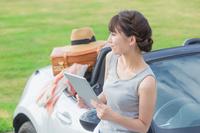 車の前でタブレットを持つ日本人女性