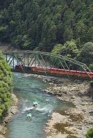 京都府 鉄橋を渡るトロッコ列車と保津川下りの船