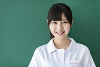 黒板の前で微笑む看護学生