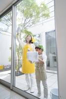 窓拭きをする中高年日本人女性と孫
