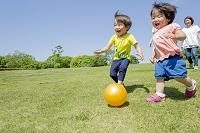 新緑の公園で走って遊ぶ日本人家族