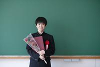 卒業証書と花を持ち微笑む男子学生