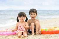砂浜に並んで座る日本人の子供