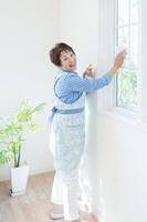 窓拭きをする笑顔の日本人のシニア女性