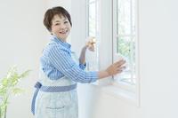窓拭きをする笑顔のシニア日本人女性