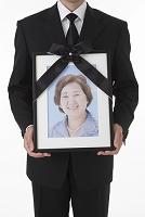 遺影を持って立つ喪服姿の日本人男性 正面