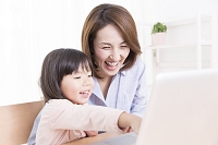 PCを操作する女の子と母親