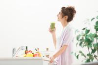 キッチンで野菜ジュースを持つ日本人女性