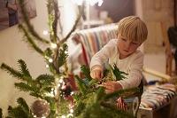 クリスマスの飾りつけをする男の子