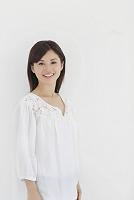 白い壁の前で微笑む日本人女性