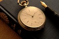 洋書の上に置かれた眼鏡 万年筆 懐中時計とコーヒー