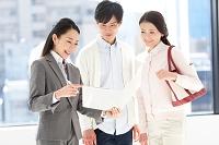 バインダーを見る日本人のビジネスウーマンと夫婦