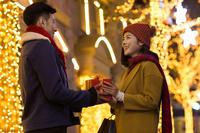 クリスマスプレゼントを渡す若いカップル