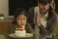 誕生日ケーキのロウソクを吹き消す日本人の女の子