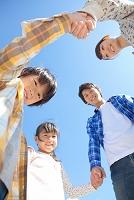 手を繋いで輪になっている笑顔の日本人家族