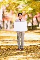 黄葉とホワイトボードを持つ男性