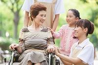 車いすに座る老人と孫と介護士